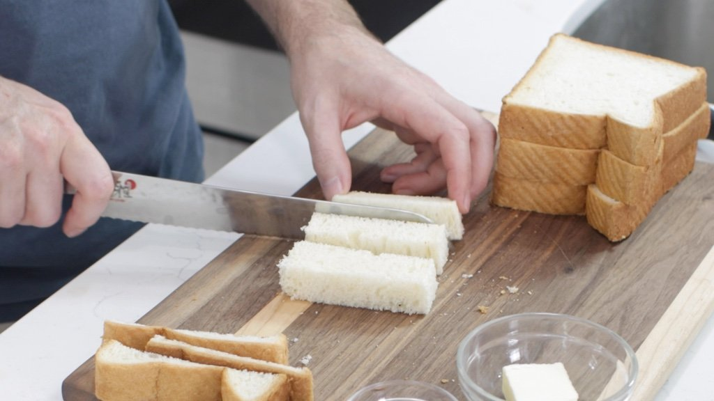 Hand slicing white thick bread.