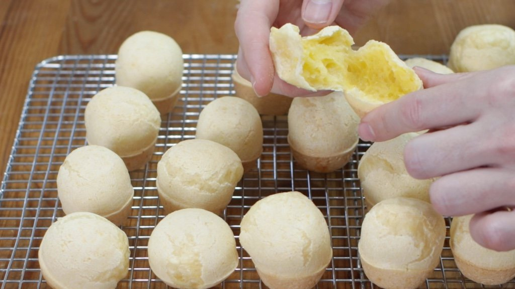 Hand pulling apart a Brazilian cheese bread