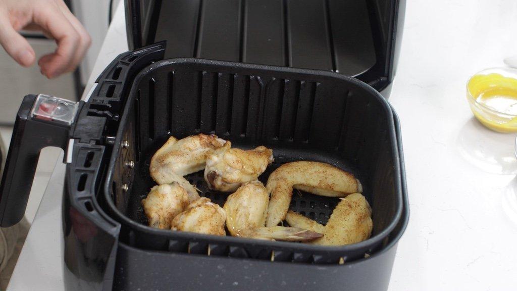 Air fryer chicken wings halfway cooked.
