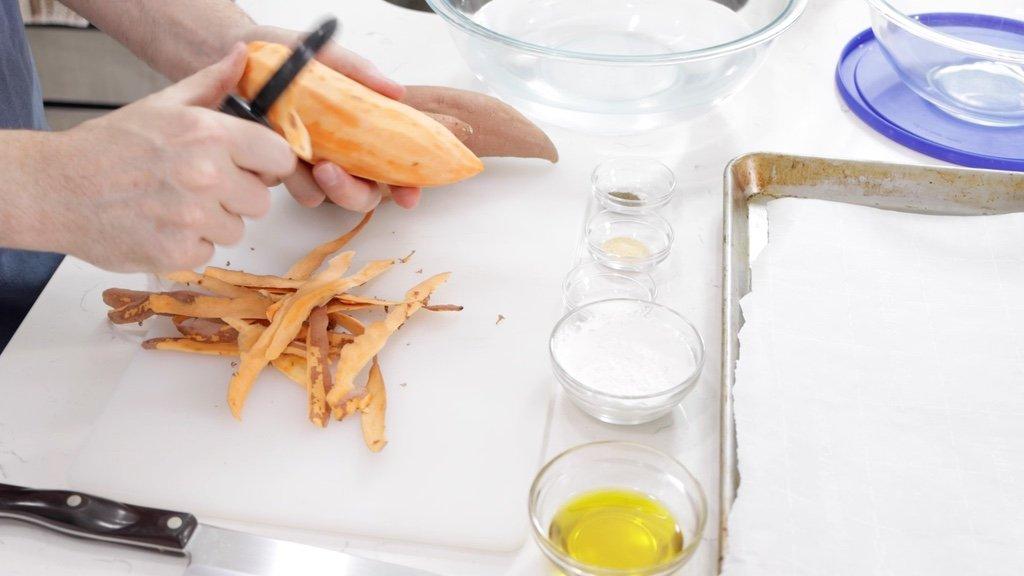 Hand peeling a sweet potato