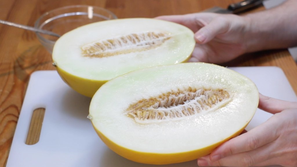 Sliced open canary melon on a cutting board.