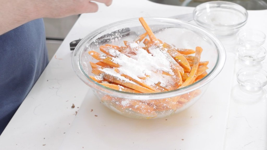 Medium glass bowl with sweet potato fries and spices.