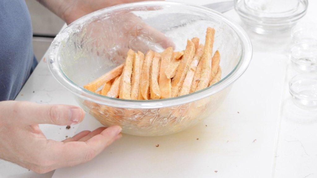 Bowl full of seasoned unbaked sweet potato fries
