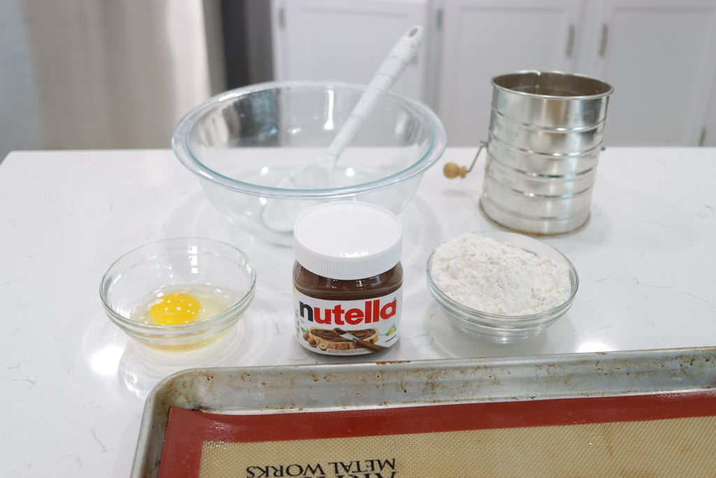 Three ingredients, egg, Nutella, and flour on a countertop.