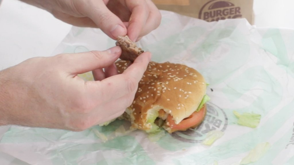 Hand holding piece of impossible whopper patty.