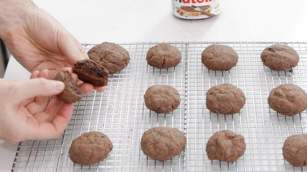 hand breaking apart a Nutella cookie.
