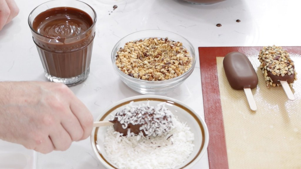 Hand dipping an ice cream bar in coconut flakes.