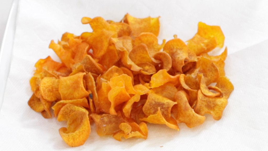 Finished sweet potato chips on a plate with paper towel.