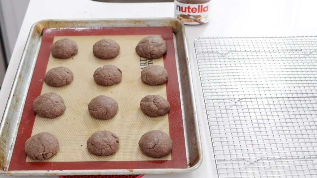 Freshly baked Nutella cookies next to a wire rack.