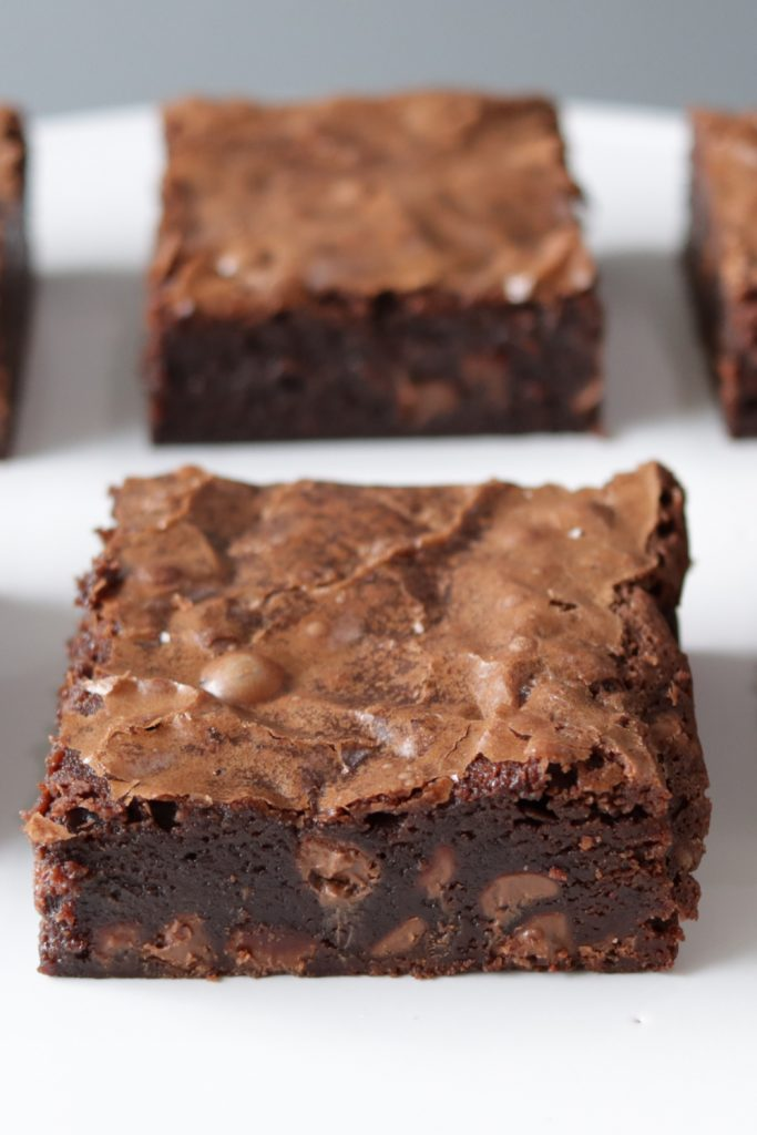 Two large fudgy brownies on a white plate.