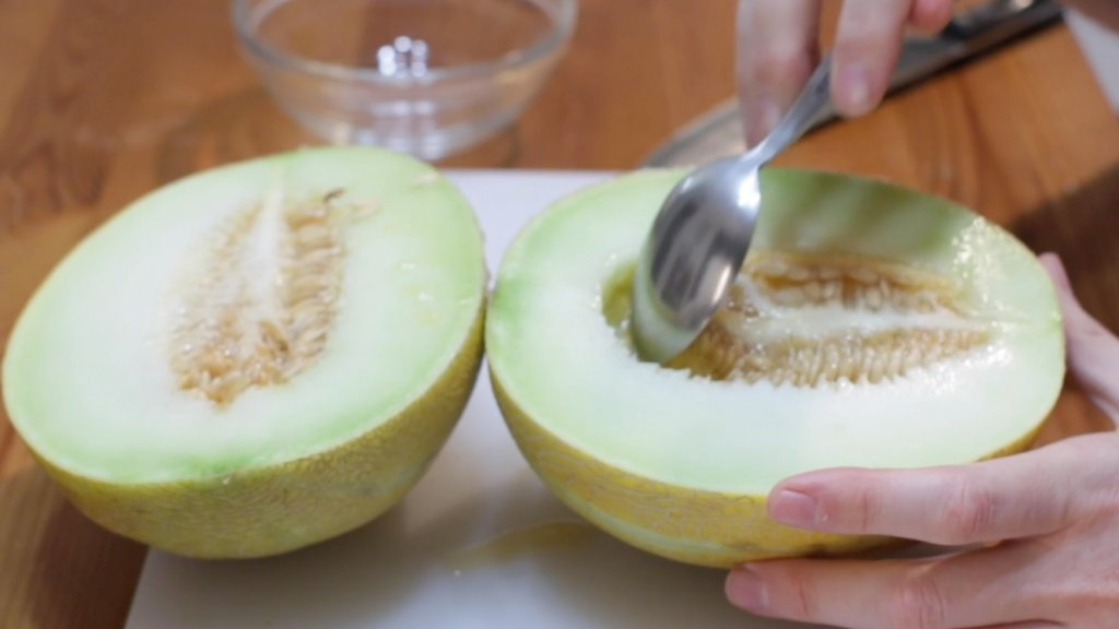 Spoon scooping the seeds out of a melon.