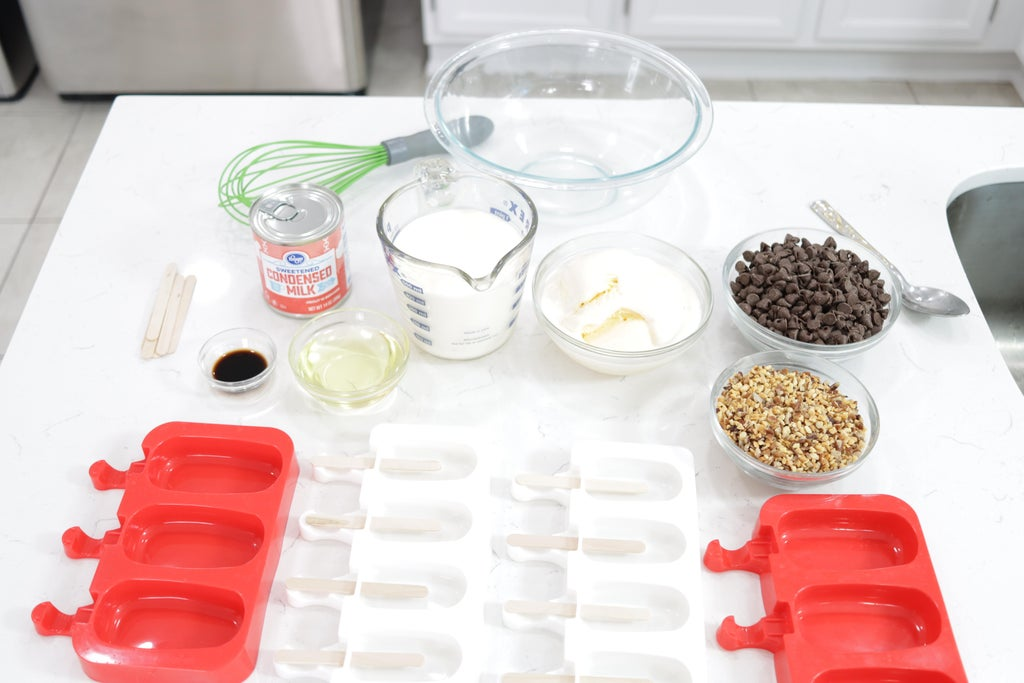 Several ingredients in glass bowls on a white counter top.