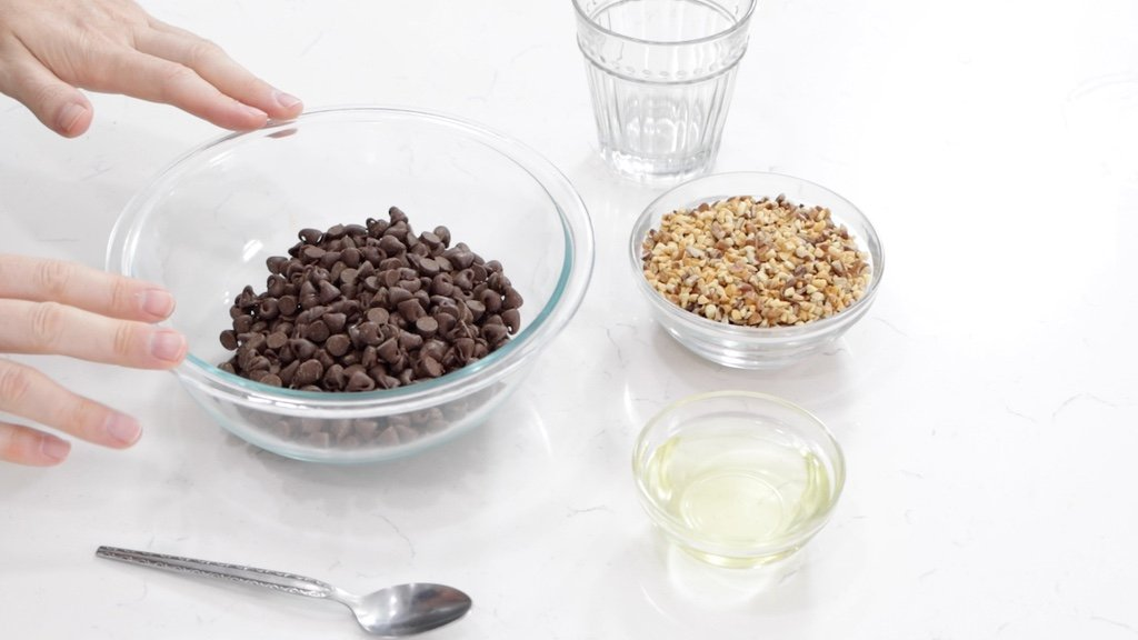 Hands resting on a glass bowl full of chocolate chips next to a bowl of nuts.