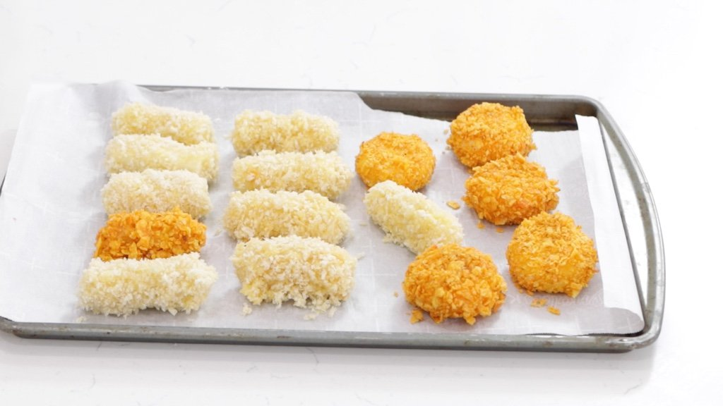 Several mozzarella cheese sticks on a sheet pan with parchment paper.