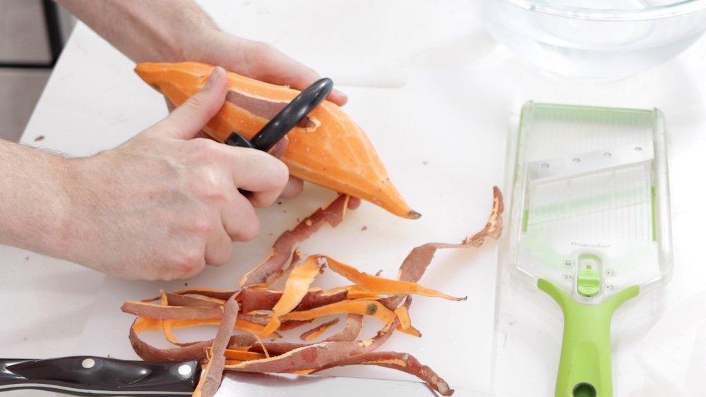 Hand peeling a sweet potato.