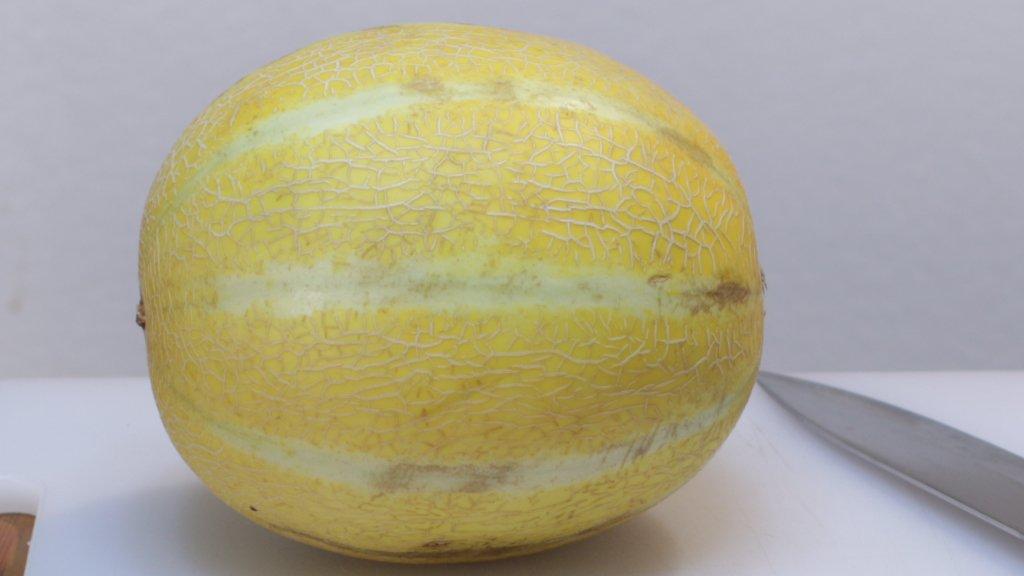 Lemon drop melon on a white cutting board next to a knife.