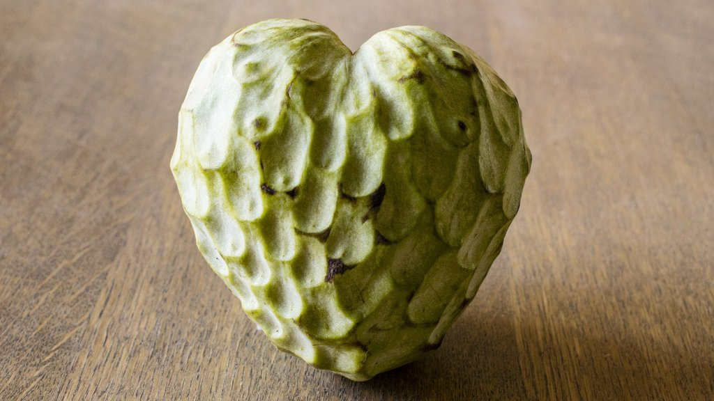 A cherimoya sitting on a wooden table.