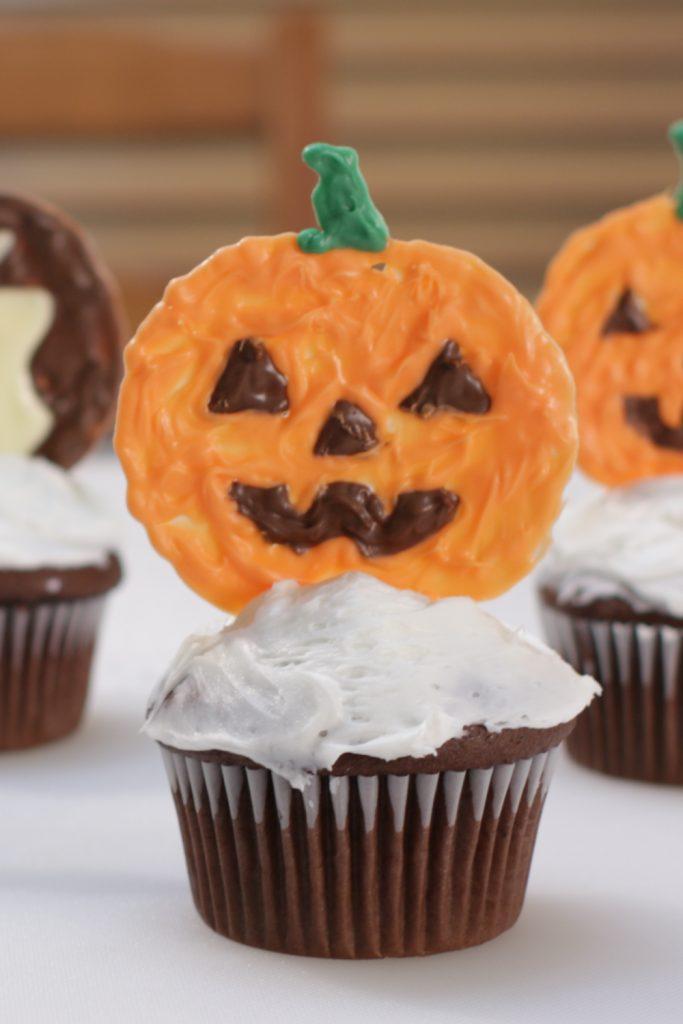 Jack-o-lantern halloween cupcake topper on a chocolate cupcake.