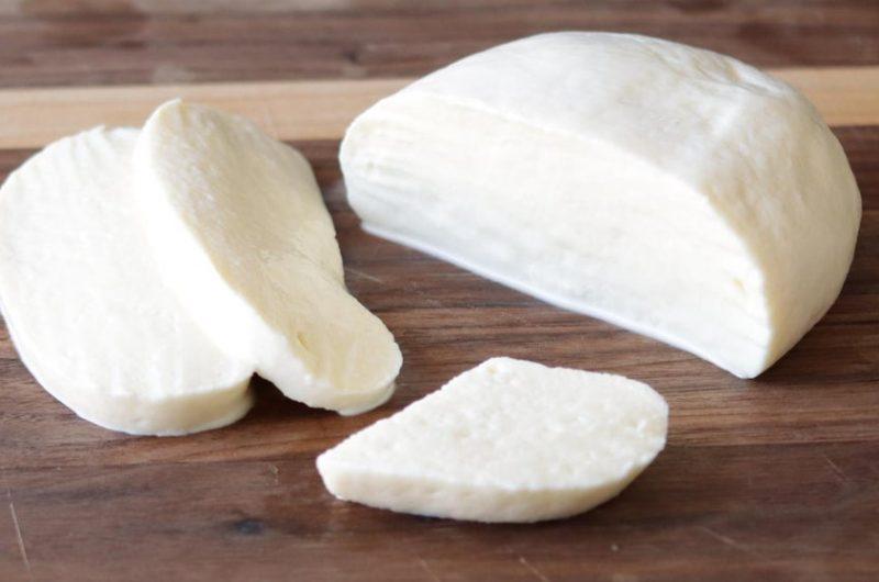Homemade mozzarella cheese on a wooden cutting board