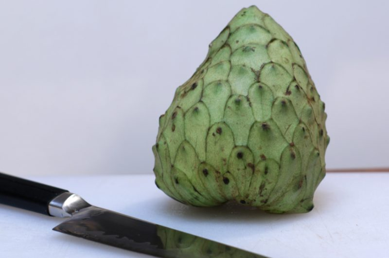 Cherimoya on a cutting board next to a knife