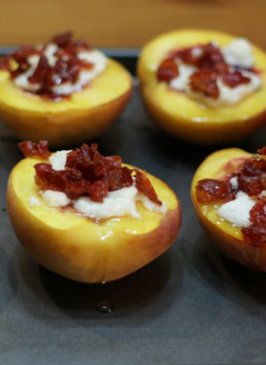 Roasted peaches on a baking pan.