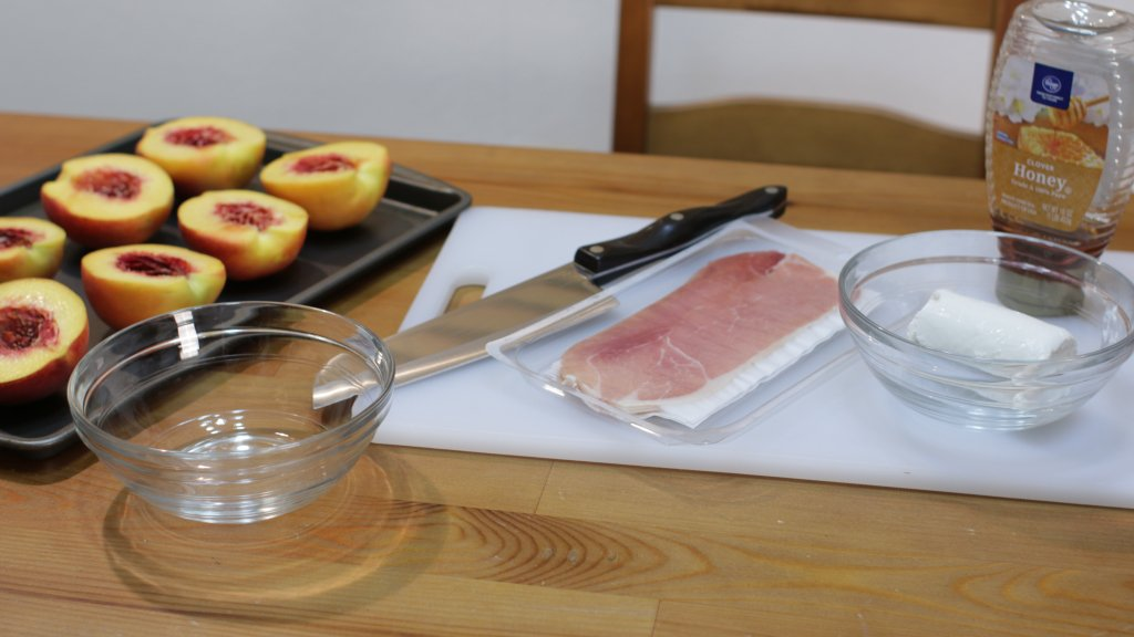 Cut peaches, prosciutto, goat cheese, and honey on a table.