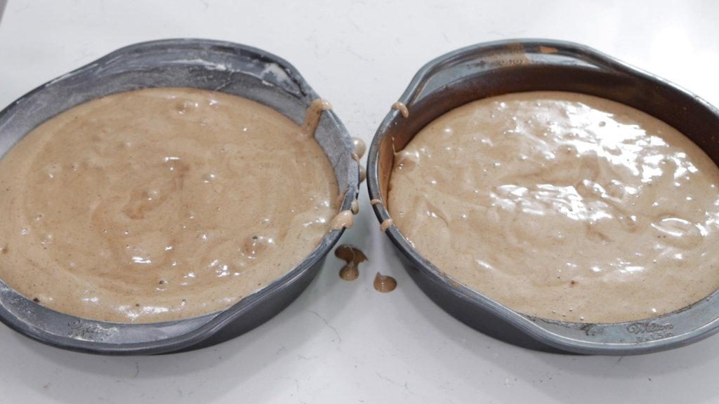 Two round cake pans filled with chocolate sponge cake batter.