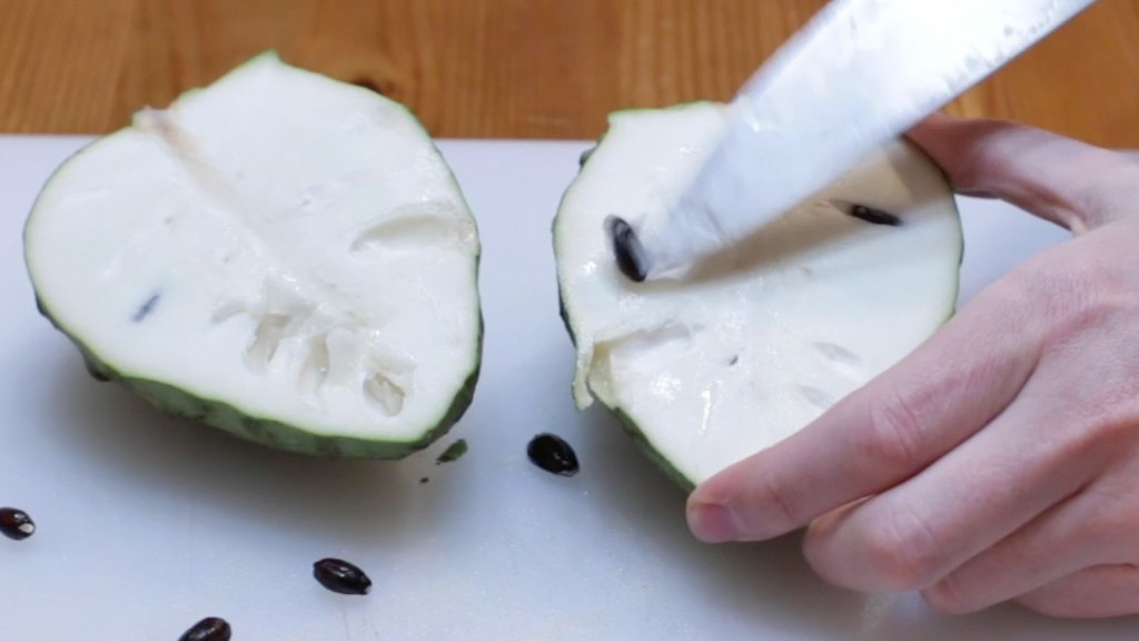 Knife cutting out the seeds of a cherimoya.