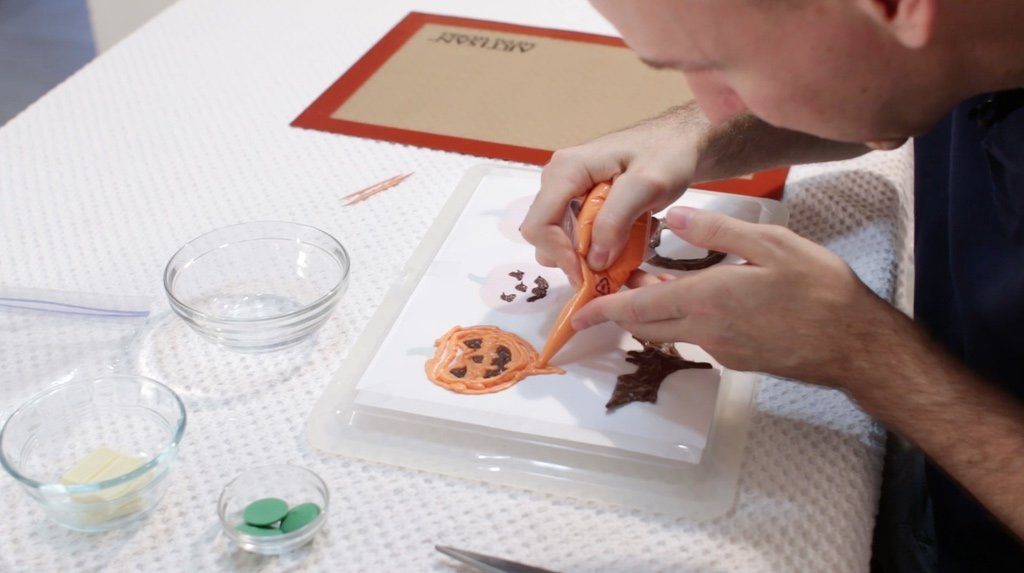 Hand using orange candy melts to fill in a Halloween stencil.