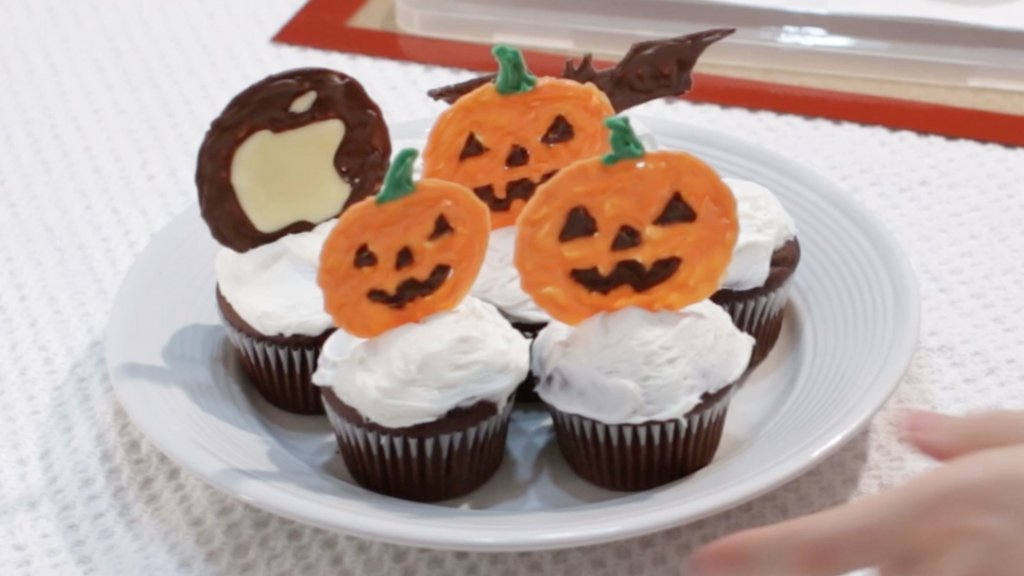 Plate full of cupcakes with Halloween cupcake toppers on them.