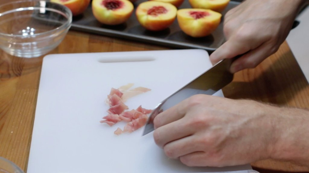 Hand slicing the prosciutto on a white cutting board.