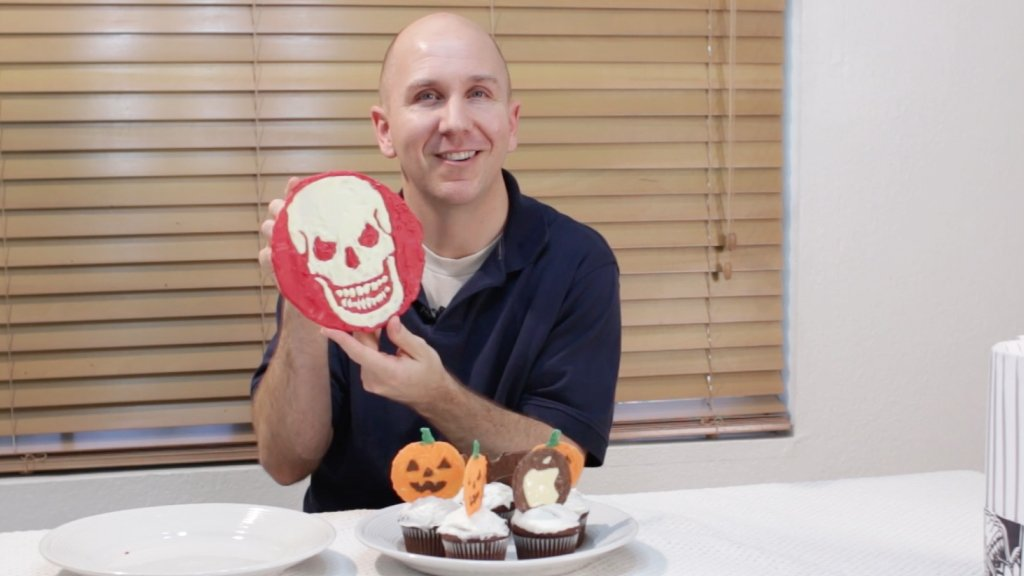 Man holding a super large chocolate cake topper.