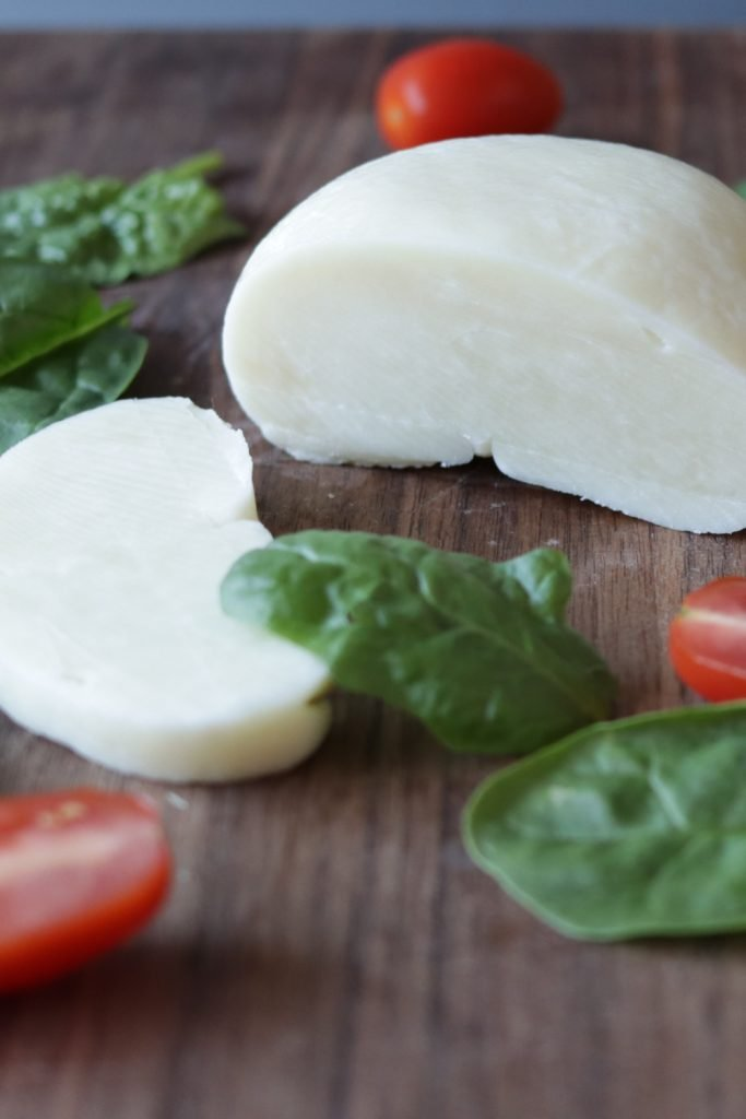 Ball of mozzarella cheese made from milk powder on a cutting board.