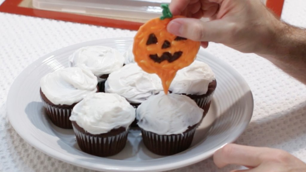 Hand placing a Halloween cupcake topper on a cupcake.