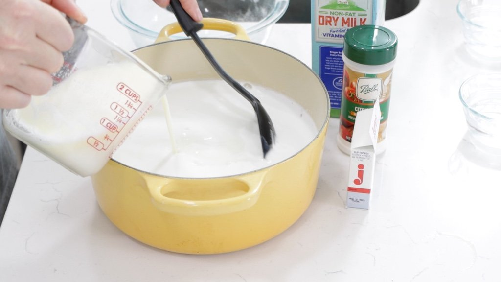 Pouring buttered milk into pot of milk.