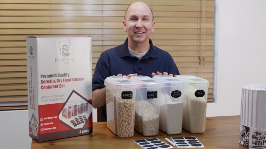 Guy sitting behind several cereal containers resting on a wooden table.