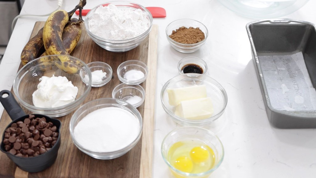 Several ingredients in glass bowls on a white countertop.