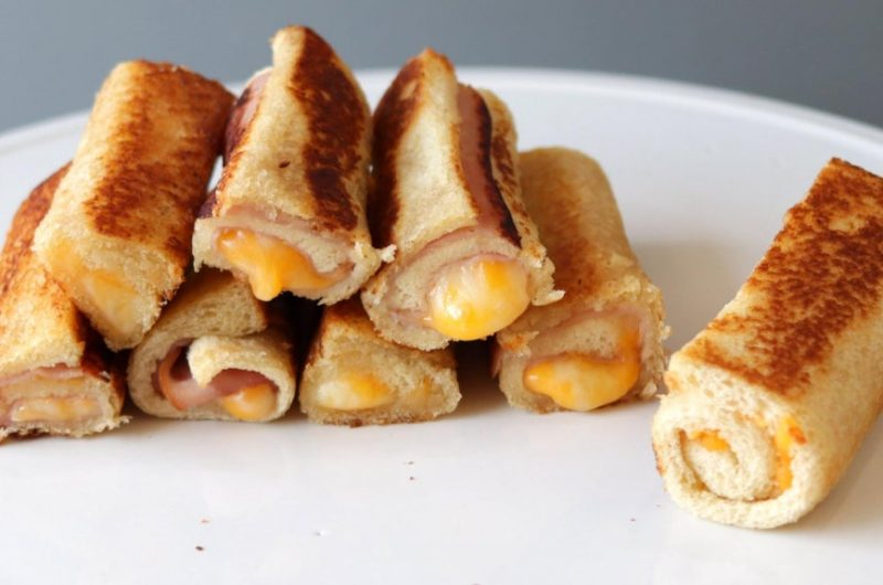 Pile of grilled cheese roll ups on a white plate.