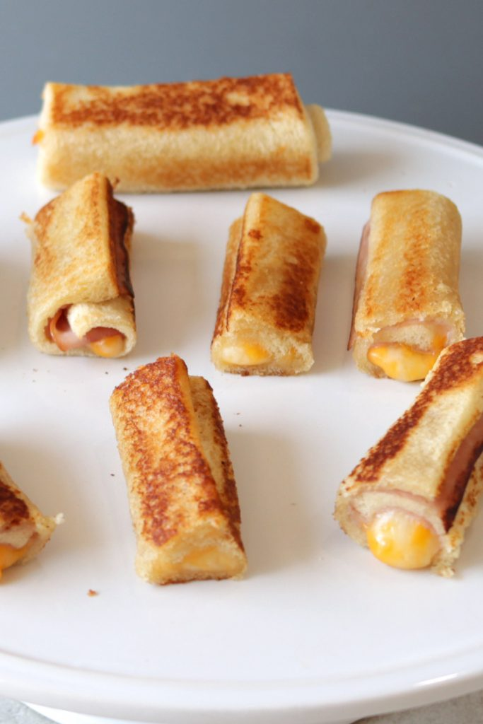 Grilled cheese roll ups on a white plate.