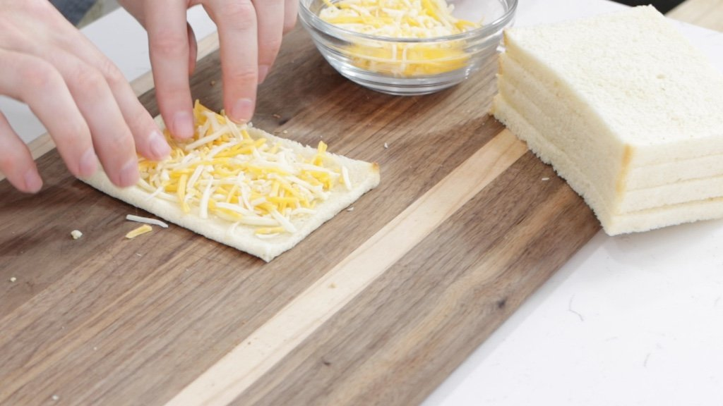 Cheese on top of a thinly rolled out slice of bread.
