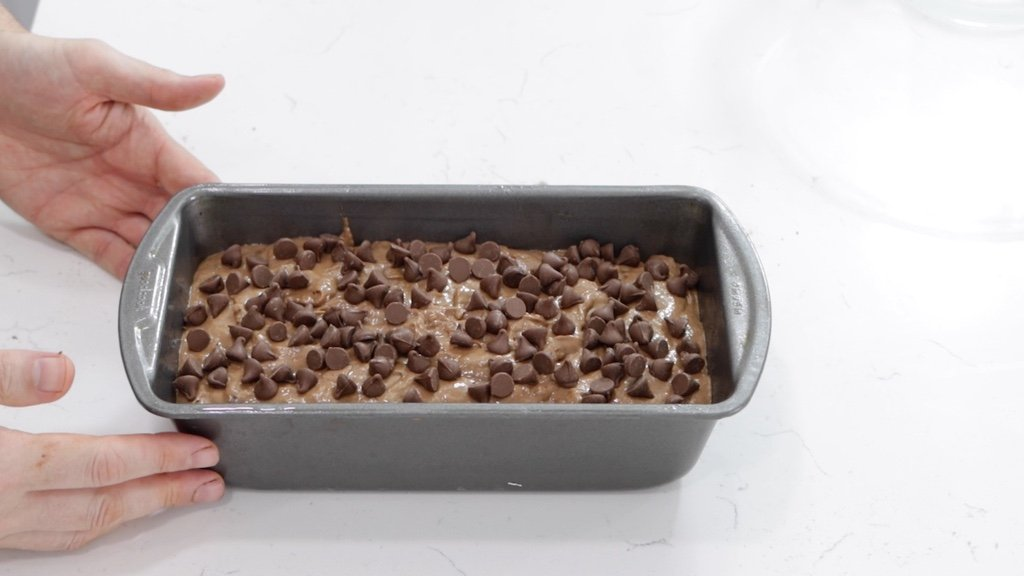 Chocolate banana bread in a greased bread loaf pan.