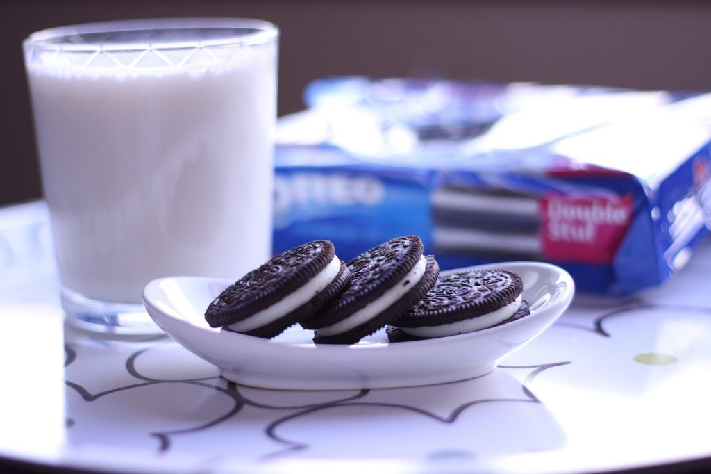 Three Oreo cookies next to a glass of milk. Number 4 most popular foods in America.