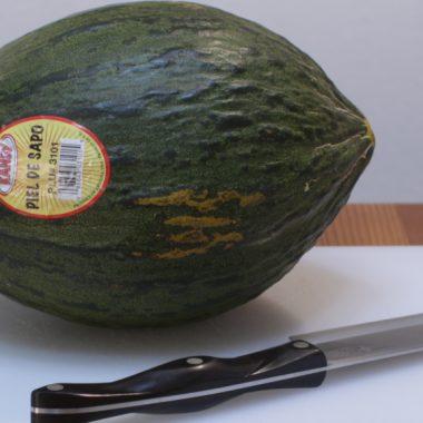 Santa claus melon on a cutting board next to a knife