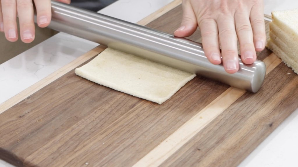 Hand rolling out the bread on a cutting board.