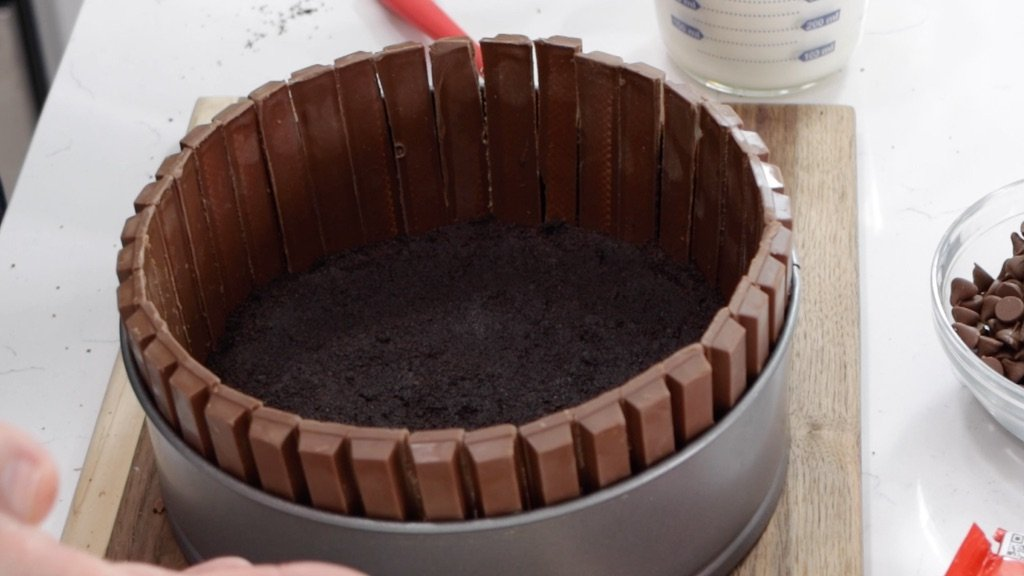 Kit Kats in a springform pan on top of a no bake chocolate cheesecake Oreo crust.