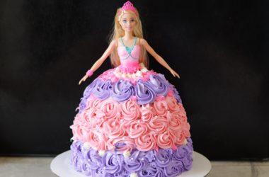 Barbie cake on a white cake pedestal.