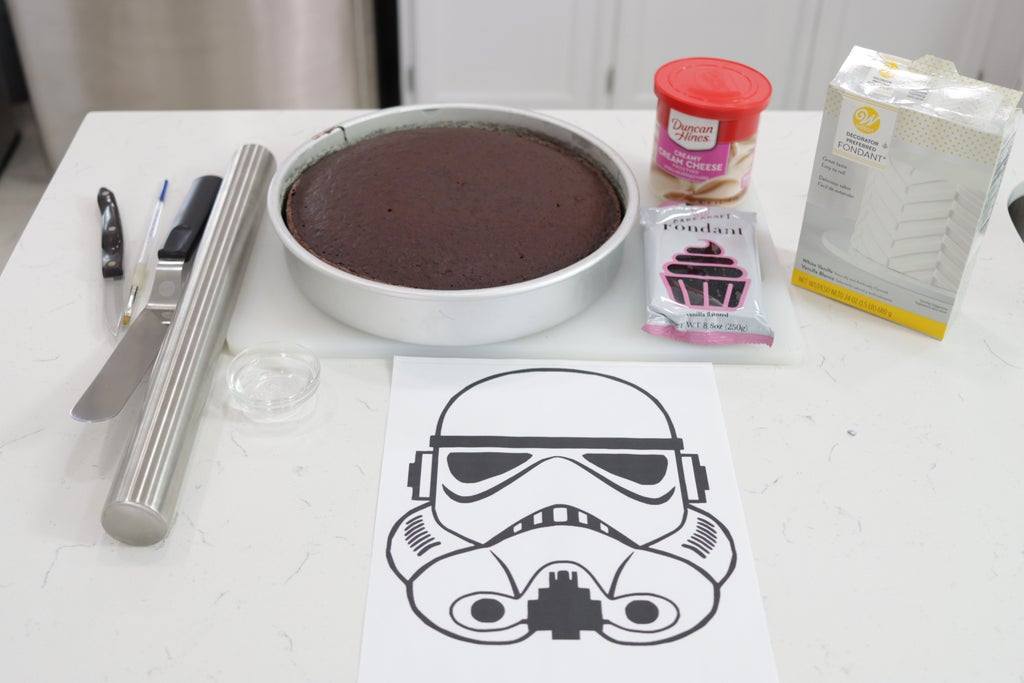 Chocolate cake in pan, frosting, fondant, and stormtrooper stencil on a counter.
