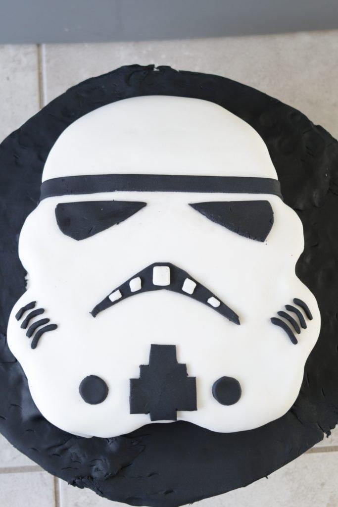 Finished Star Wars Cake Stormtrooper laying on black fondant.