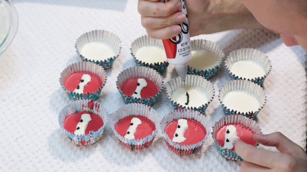 Hand piping faces on the baymax peanut butter cups