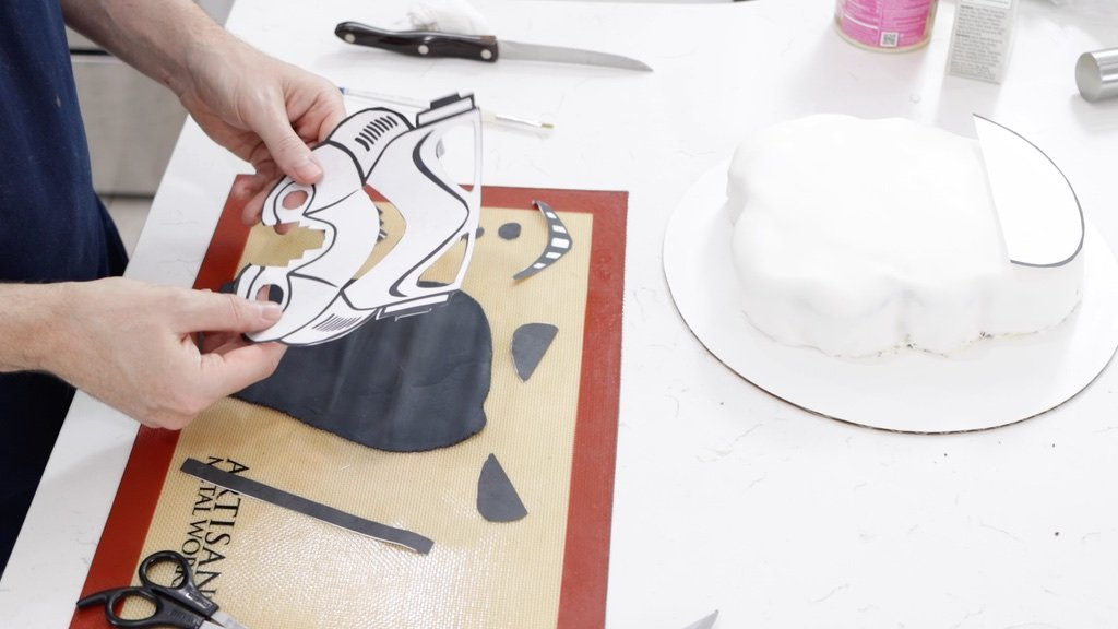 Hand holding a star wars cake stormtrooper head stencil with pieces cut out of it.